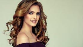 有长篇,发光和卷曲发型的棕色毛发的妇女 卷曲的头发 免版税库存图片