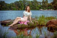 有长红色头发放松的美丽的少妇,坐一个岩石在池塘 免版税库存照片