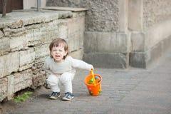 有长金发哭泣的站立的小男孩在街道上 在他的手上他在沙盒拿着橙色桶使用 库存图片