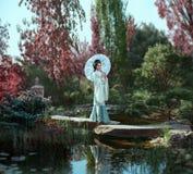 有长,黑发的一名年轻日本妇女用Kandzashi、花和长的簪子装饰了有水晶小珠步行的 库存图片