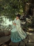 有长,黑发的一名年轻日本妇女用Kandzashi、花和长的簪子装饰了有水晶小珠步行的 免版税图库摄影