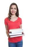 有长黑发看和书的愉快的女学生 库存照片