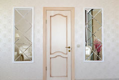 有门和两相称镜子插入物的客厅墙壁 免版税库存照片