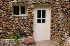 有门和窗口的石被设计的墙壁 库存图片