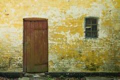 有门和窗口的黄色墙壁 库存照片