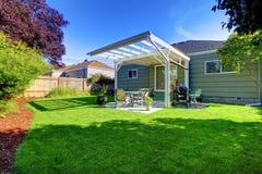 有门廊和后院的绿色小屋。 图库摄影