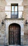 有门廊的一个老房子的门户和阳台有为支架入口使用的钉子加强的木门的 免版税库存图片