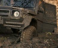 有门户开放主义陷进的肮脏的越野汽车在深车轮痕迹 库存照片