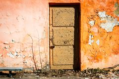 有门的老橙色墙壁 免版税库存图片