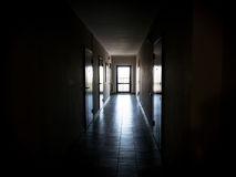 有门的长的黑暗的走廊对公寓 免版税图库摄影