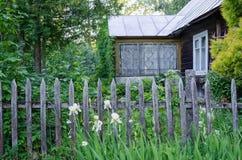 有门廊和土气木篱芭的古国房子 免版税图库摄影