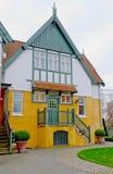有门廊的白橙色房子 免版税库存图片