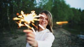 有闪烁发光物的庆祝在海滩党的年轻微笑的妇女画象  免版税库存图片