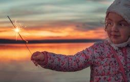 有闪烁发光物的美丽的女孩在日落的湖 库存图片