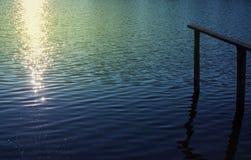 有闪耀的光的美丽的码头水表面上 库存照片