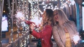 有闪耀的烟花的美丽的女孩在夜城市庆祝一个假日并且获得乐趣 慢的行动 股票录像