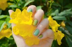 有闪闪发光绿色修指甲的妇女手 免版税库存照片