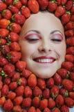 有闭上她的在草莓背景的空白牙的新美丽的妇女眼睛 库存照片