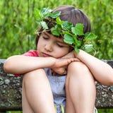 有闭上她的眼睛的叶子冠的平安的孩子睡觉 免版税库存图片