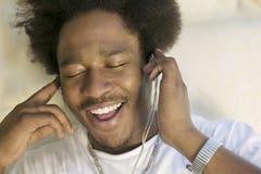 有闭上的眼睛的人享受音乐通过耳机 库存照片