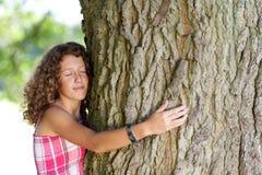 有闭上的眼睛的女孩拥抱树 免版税库存图片