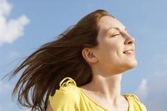 有闭上的眼睛的妇女享受阳光反对天空 免版税库存图片