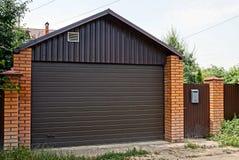 有闭合的棕色门和篱芭的私有房子在一条农村街道 库存照片