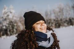 有闭合的眼睛的女孩享受冬天森林的宁静和寂寞的 免版税库存照片
