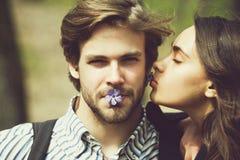 有闭合的眼睛的女孩亲吻面颊的帅哥 库存图片
