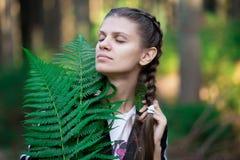 有闭合的眼睛的女孩在森林里 免版税库存图片