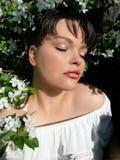 有闭合的眼睛的妇女取暖在阳光的 库存图片