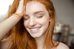 有闭合的眼睛的微笑的红头发人妇女 图库摄影