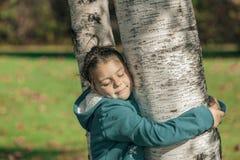 有闭合的眼睛的愉快的小女孩,拥抱桦树在秋天公园和享受她的业余时间在晴朗的温暖的天 免版税库存图片