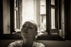 有闭合的眼睛的沉思少妇在放松和作梦在黑白颜色的被打开的窗口附近的想法丢失了在vintag 库存图片
