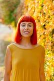 有闭合的眼睛的美丽的红发妇女在公园 库存照片