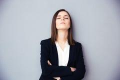 有闭合的眼睛的年轻女实业家在灰色背景 免版税图库摄影