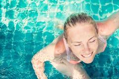 有闭合的眼睛的年轻美丽的轻松的妇女从乐趣喜欢游泳在游泳池的绿松石水中与拷贝空间 免版税库存图片
