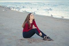 有闭合的眼睛,长的头发的年轻美丽的妇女,在黑牛仔裤和红色衬衣,坐在海滩的沙子在海鸥鸟中 库存图片