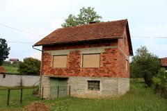 有闭合的窗帘和被毁坏的木车库门的未完成的被放弃的红砖家庭房子围拢与未割减 库存图片