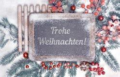 有问候文本的黑板用德语和圣诞节装饰 免版税图库摄影