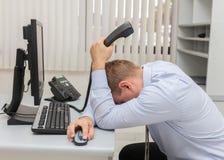 有问题和重音的年轻商人在坐在计算机前面的办公室 库存图片