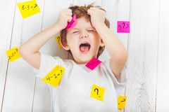 有问题标志的哭泣的孩子与在他的头的贴纸和 免版税图库摄影