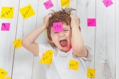 有问题标志的哭泣的孩子与在他的头的贴纸和 库存图片