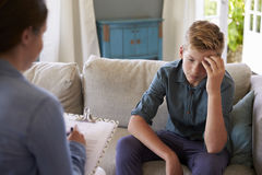 有问题的十几岁的男孩在家谈话与顾问 免版税库存图片