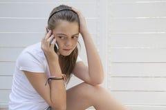 有问题的可爱的十几岁的女孩联系由电话。 免版税库存照片
