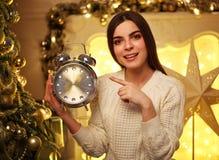有闹钟的女孩在家在圣诞节装饰 免版税库存照片