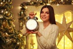 有闹钟的女孩在家在圣诞节装饰 库存图片