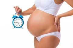 有闹钟的怀孕的腹部 背景黑色概念概念性费用房主房子图象挣的货币表示 很快诞生 胚胎发育在几个月之前 库存图片