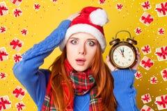 有闹钟的红头发人女孩 库存图片