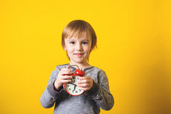 有闹钟的逗人喜爱的小男孩在黄色背景 库存图片